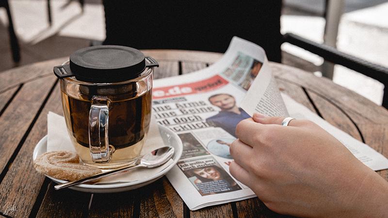 Zeitung mit Tee und Hand_web.jpg
